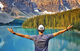 Man with outstretched arms facing lake and mountains