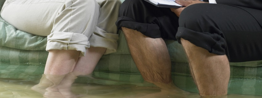 Couple with pants rolled up standing in flooded room