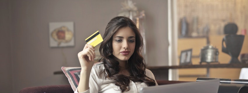 Woman holding credit card looking at computer